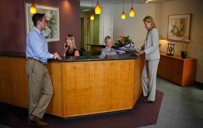 four people at front desk of office